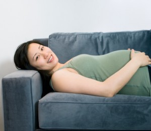 Pregnant Asian woman laying on sofa